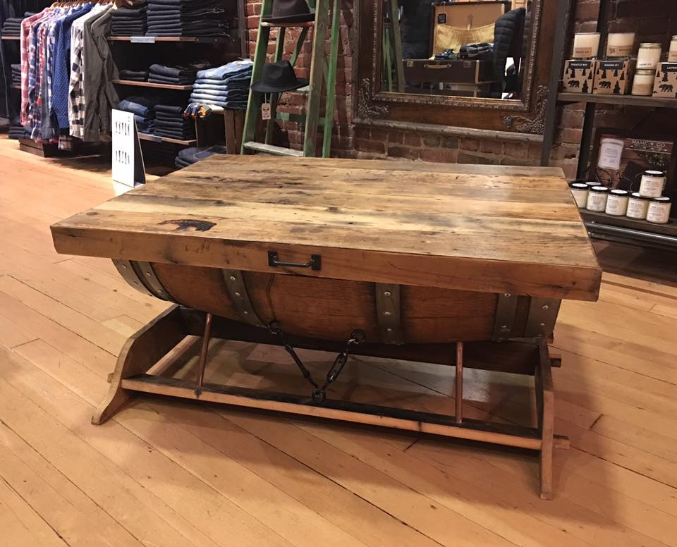 This coffee table is made from half of a wine barrel with a barn wood top.