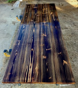 Handmade pine table made from pine. The dark grain in the wood was a result from burning the wood.